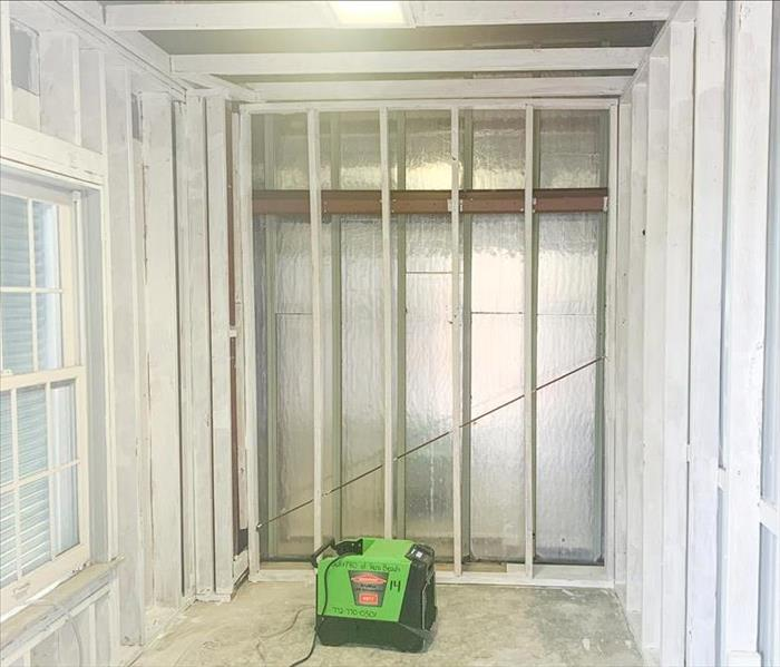 room with window without any dry wall, completely bare. SERVPRO dehumidifier is on the ground