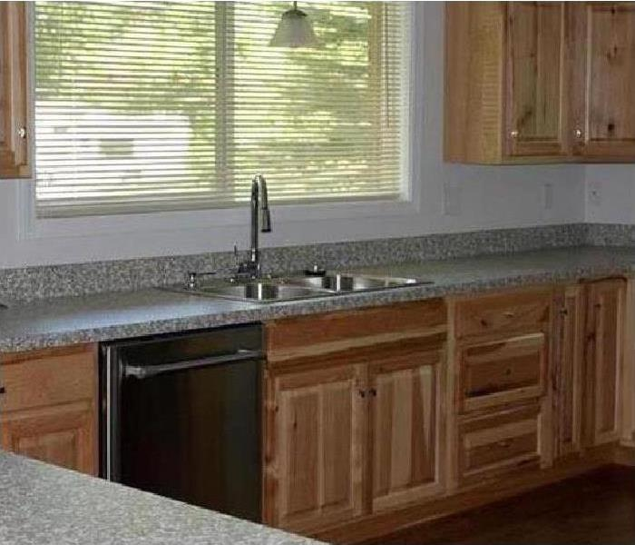 Kitchen restored with new wood cabinets and stainless-steel appliances.