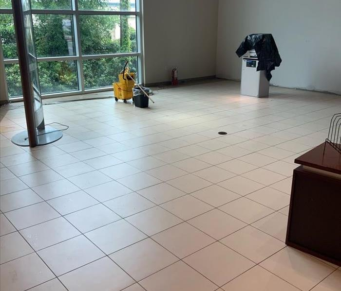 Clean and dried white tile floor inside showroom of car dealership.