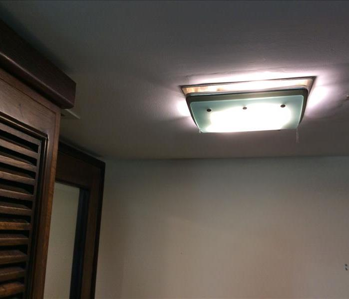 Bathroom light fixture with water stains on the ceiling around it