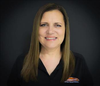 White female with brown hair wearing a black SERVPRO shirt and smiling