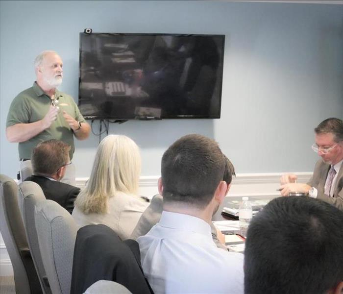 Insurance agents gathered in a conference room listening to Jimi Tunstall teach about SERVPRO