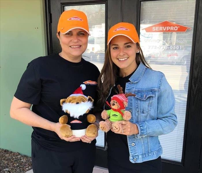 2 ladies holding SERVPRO Teddy and Bulldog
