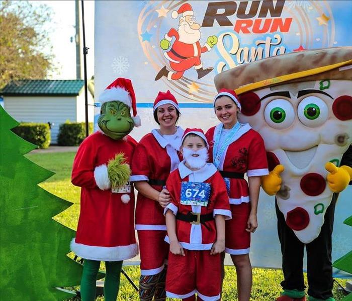 3 runners dressed up as Santa posing for a picture