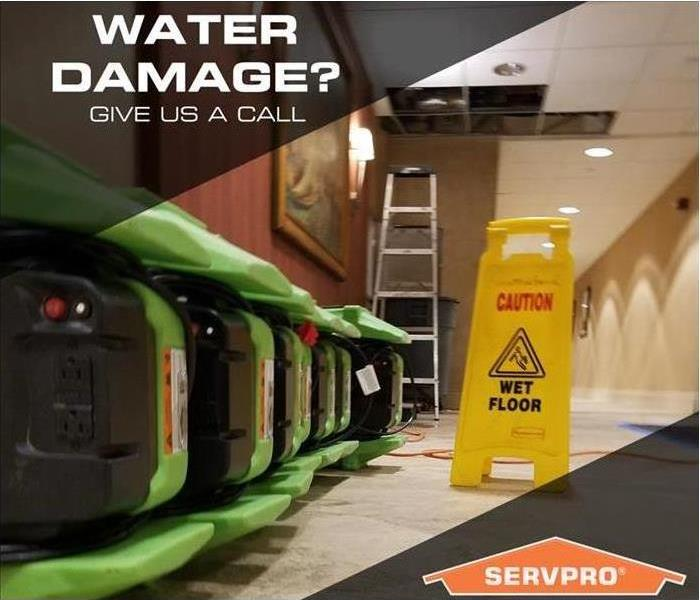 "Air movers lined up in a hallway with the words ""Water Damage? Give us a call."""
