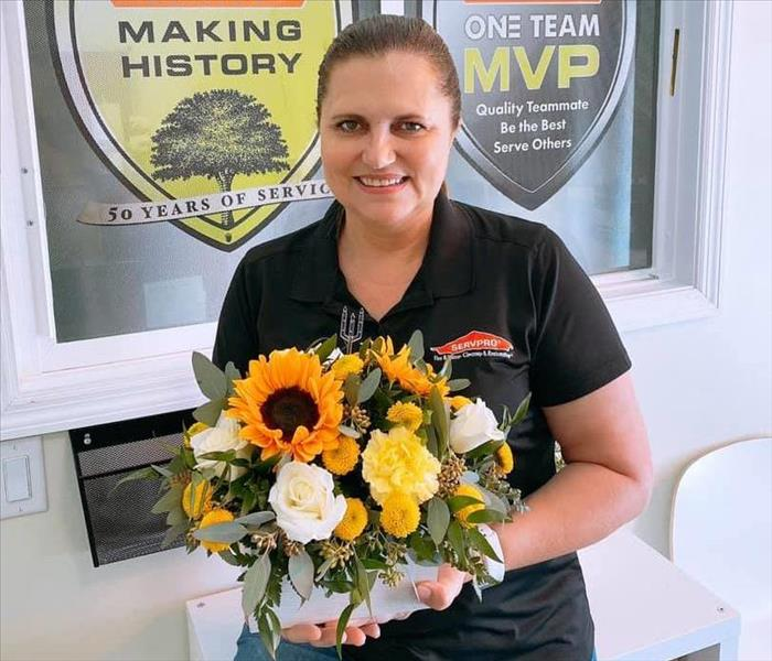 Woman with brown hair and black shirt holding a bouquet of sunflowers and other greenery