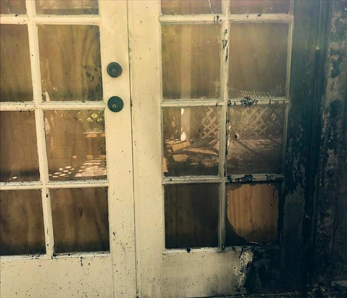 Front of a door burned by fire, and a window pane broken through