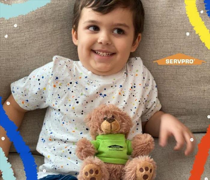 SERVPRO Teddy bear sitting on couch next to boy in multi colored shirt