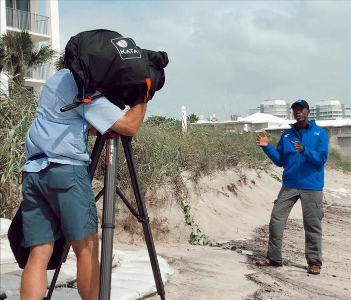 weather man on beach being recorded by a man with a big camera