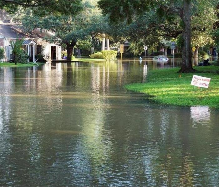 Flooded street with a white home in the background and small patch of green grass on the right hand side