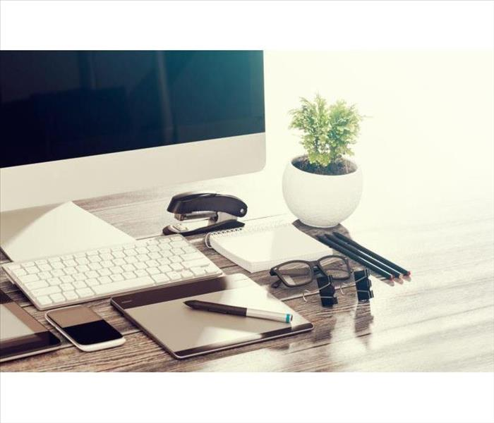 Closeup view of a desktop with a computer, keyboard, small plant, reading glasses, and notepad and pen, stapler and phone