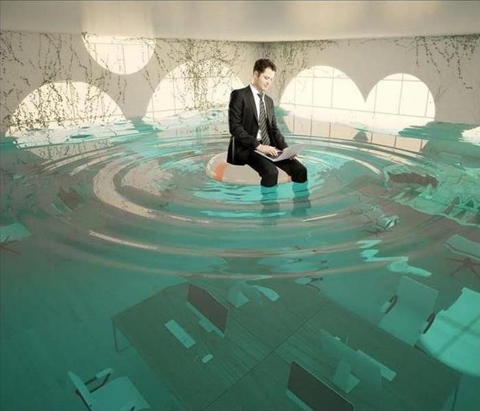 Stock photo of a man sitting on a pool float, working on his laptop, inside a flooded office.