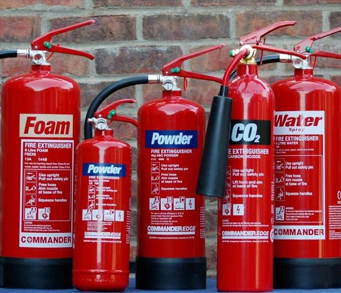 Five fire extinguishers of various sizes lined up in front of a brick wall