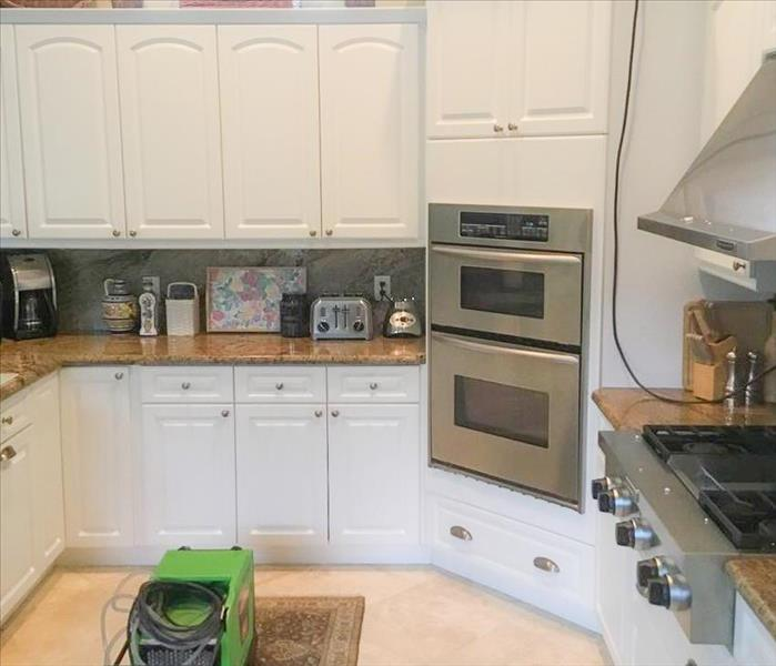 Clean kitchen in home with white cabinets. SERVPRO equipment dehumidifier and air mover are finishing up the work