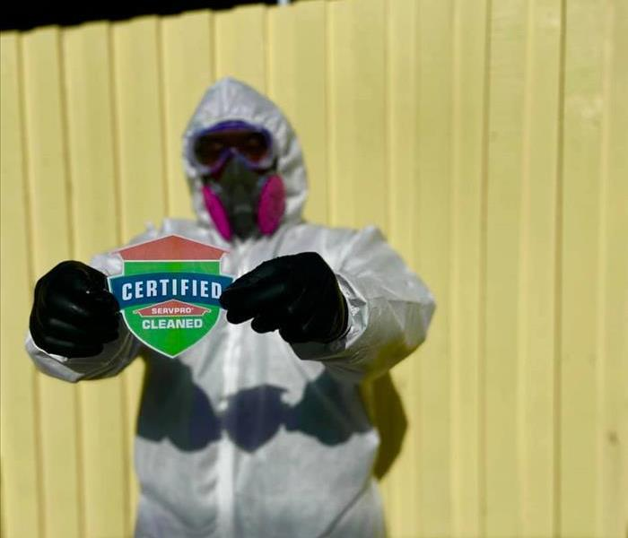 Man in full PPE holding up the Certified: SERVPRO Cleaned shield.