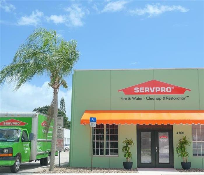 front of SERVPRO building on a sunny day, surrounded by SERVPRO truck and palm trees