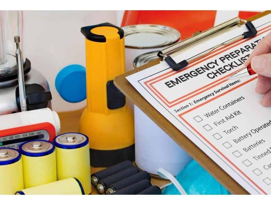 Clip board with disaster supply checklist and flashlights, batteries, and canned foods in the background