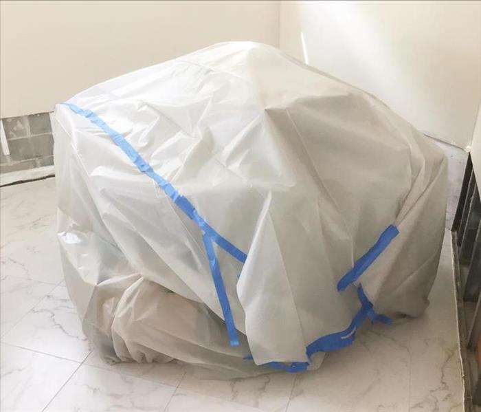 Pile of customer's furniture placed in center of room, covered in a white tarp