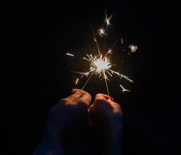 A man holding up a sparkler in each hand.