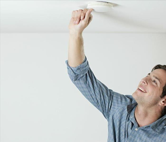 White man pressing test button on smoke alarm.