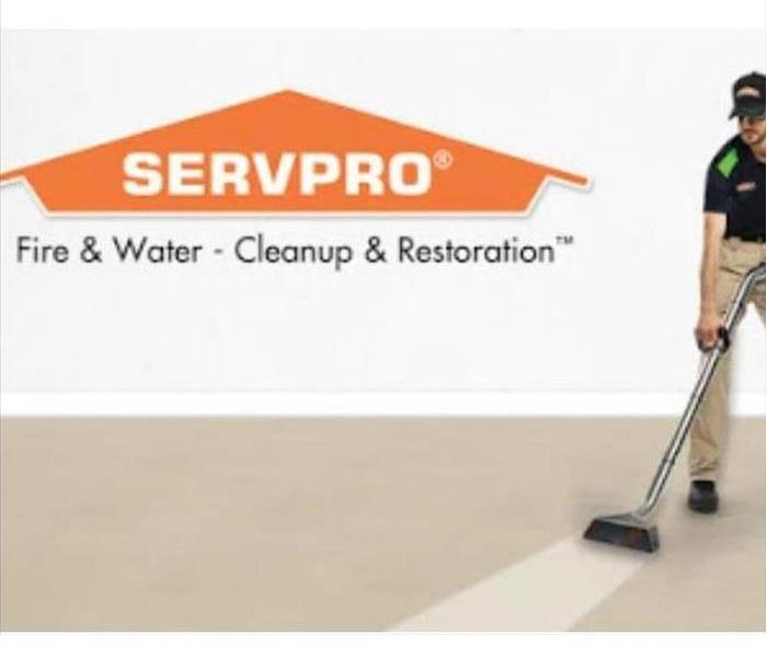 Man in SERVPRO uniform cleaning carpet. Servpro logo is in the top left hand corner.