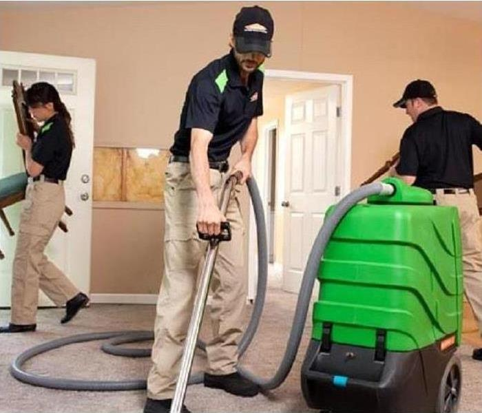 Three SERVPRO employees cleaning a room in a home. Two are moving furniture, the third is cleaning the carpet.
