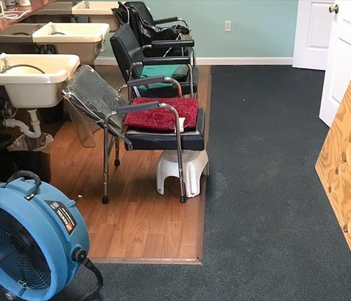 Three hair salon chairs and sinks in a salon with SERVPRO equipment